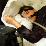 A man asleep with his CPAP oxygen machine